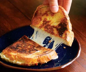 Grilled cheese cut in half on a plate. A hand is pulling one of the halves up and large strings of cheese connect the two pieces