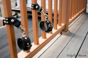 A pair of leather bondage cuffs attached to a balcony railing
