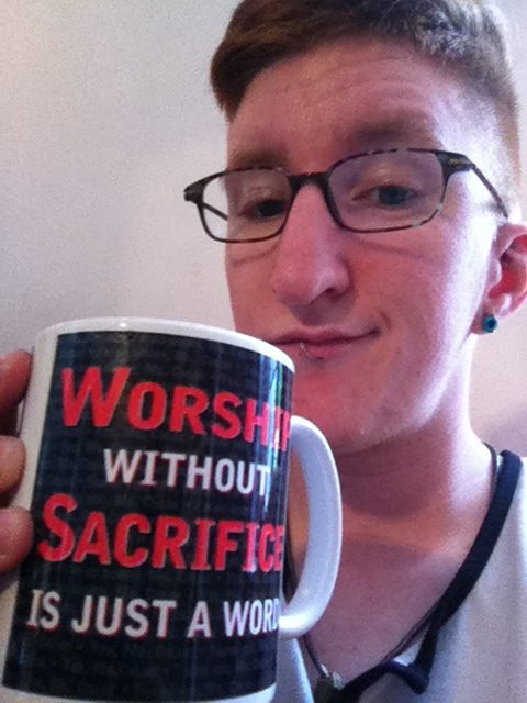 "Taylor on Set of First Porn Shoot. They are smirking and holding a mug that says ""Worship without Sacrifice is just a word"""