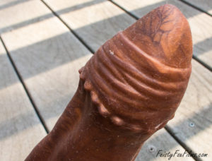 Exotic Erotics Wraith dildo, the head appearing in the upper right corener of the screen. The shot focuses on the texture at the base on the head and the pointed ridge.