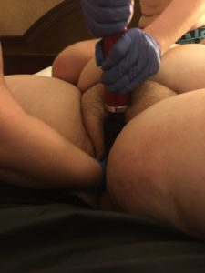Sugar Cunt's legs spread wide, someone's fist in their cunt as Taylor holds a red Doxy to their clit