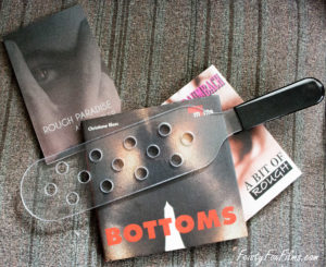 "MEO's Bulletproof Paddle with Holes sits on top of three books; ""BOTTOMS"", ""A Bit Rough"", and ""A Rough Paradise""."