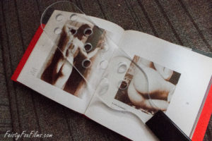MEO's Bulletproof Paddle with Holes lies on top of an open book. The book is open to two pages featuring naked people (specifically their butts), and can be seen through the paddle
