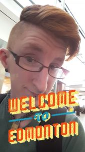 "Taylor smirks sleepily at the camera. A brightly-coloured pop art filter is across the bottom of the image saying ""Welcome to Edmonton"" on it"