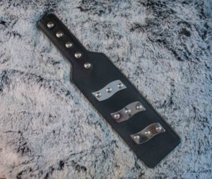 The Electro Spanking Paddle lies diagonally on top of a grey and white fake fur material. The three rows of electrodes are very shiny.