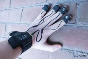 My hand is braced against a brick wall, the Hello Touch X strapped to my wrist. The etwo sets of attachments are on my fingertips on the outside of my hand.
