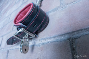 One Padded Lockable Cuff hangs from a brick wall. It is closed and there is a pretty lock securing it in place.