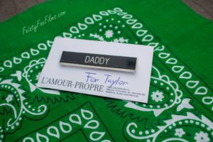 "A pin saying ""Daddy"" ontop of white cardstock denoting it as being ""for Taylor"". The carstock sits ontop of a hunter green flagging hanky, the colour for daddies/people wanting daddies"