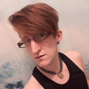Taylor stands in front of a clear shower curtain. Their hair is freshly cut and hanging perfectly straight over their left eye. They're wearing glasses, a black mesh tank top, and their collar, and they have a serious expression on their face