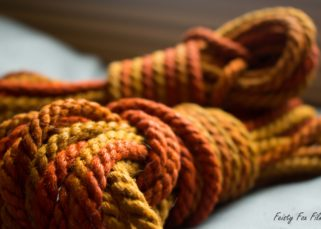 A few pieces of hemp rope lie on top of each other, the colours ranging from deep orange to light yellow and back.