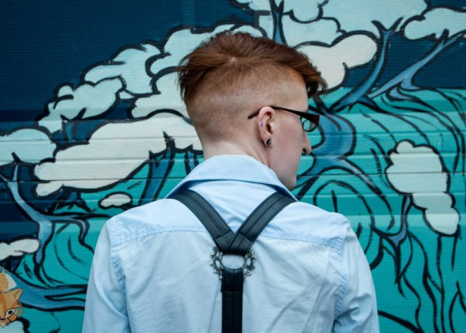 Taylor stands facing a garage door with some sort of blue and green painting on it. They're wearing a light blue button-up shirt, black bike tube suspenders with a metal gear in the center. Their hair is shaved on the sides and back, a bit longer on the top.