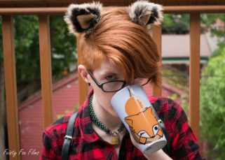 Taylor shown from the chest up sitting in front of a wooden fence overlooking trees and a garage. They are wearing a red plaid button-up, a black leather chest harness, and their collar. They're drinking out of a mug with their site's fox logo on it while looking intensely into the camera. Their hair is short on the sides and long on the top, slightly wavy and pushed to one side and they're wearing clip-on fox ears.