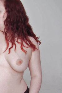 The right side of a pale white person with died red hair is shown from the waist up. They are naked except the hint of underwear, chest exposed, face blurred out.