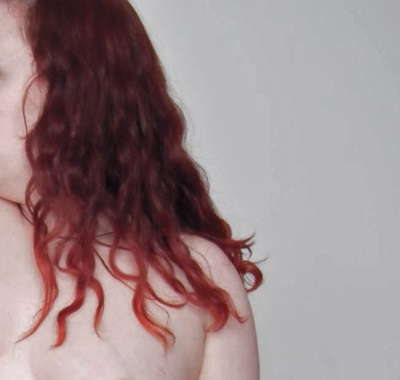The right side of a pale white person with died red hair is shown from the chest up. They are topless and their face is blurred out.