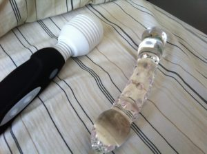the mystic wand and a glass dildo lie side by side on a bed