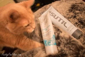 an orange cat kneeds a blanket next to a bottle of Slippery Stuff and a bottle of Sutil lubes