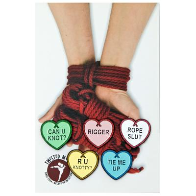 a collection of heart-shaped enamel pins with rope-themed sayings on them on top of hands holding red bondage rope